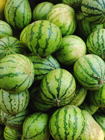 Many green and small watermelons in the open market