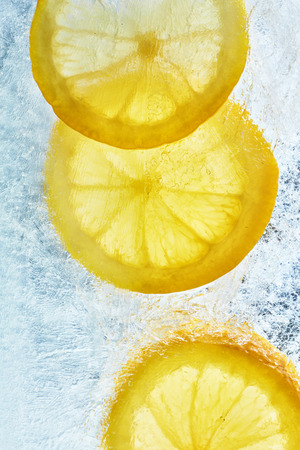 refrigerator: Lemon on the ice. Refreshing summer background of citrus. Yellow lemons and ice photo from above.