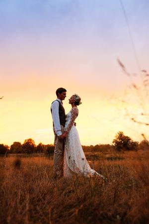De bruid en bruidegom staan ??aan het meer, na de huwelijksceremonie. Jonggehuwden glimlachen, ze zijn gelukkig. Gesilhouetteerde foto in warme kleuren. Backlight.