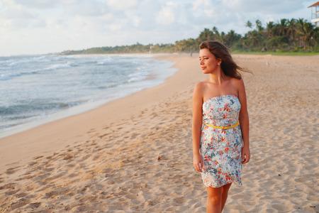 Meisje in een jurk wandelen langs het strand in de buurt van de Oceaan en op zoek naar de horizon