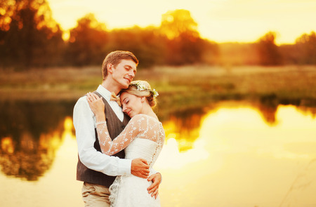 The newlyweds are hugging on the lake at sunset. The lake reflects the sky and trees