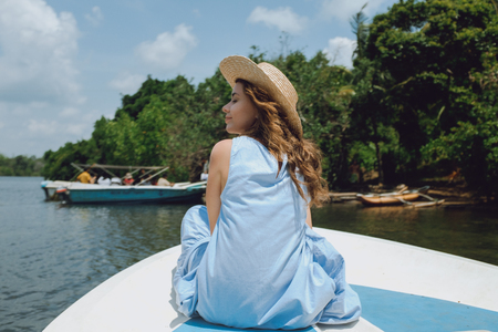 A young woman in a hat and blue dress is sitting on the bow of the boat and sailing along the river Stock Photo