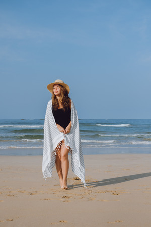 Girl in a hat covered by a beach towel walking along the ocean shore