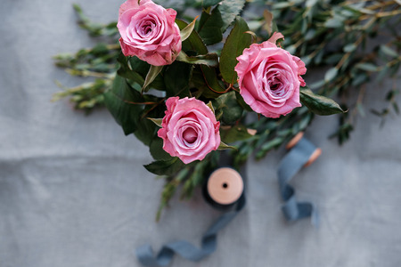 Pink roses, eucalyptus on gray flax