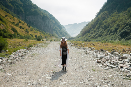 A girl in a hat walks along the middle of the road towards the mountains in the valley in the mountainous country of Georgia
