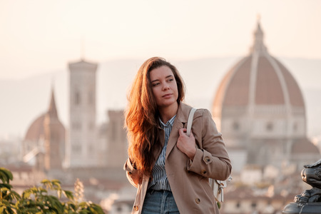 Journey to Italy. The girl is sitting with a view of Florence. Cathedral of Santa Maria del Fiore on the background.