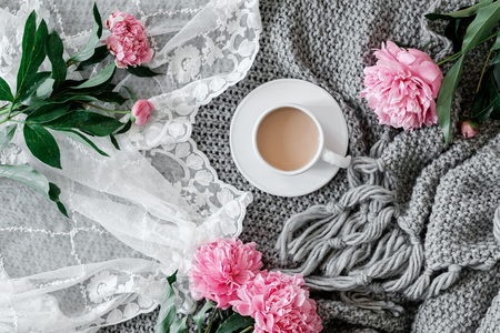A cup of coffee and peonies on a gray background. Flat-lay of cup of coffee with  peonies Stock Photo