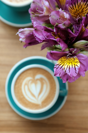 Lilac alstroemeria flowers on the table with a cup of coffee