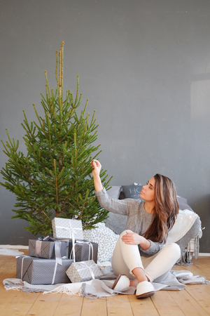A young woman sits under a Christmas tree with gifts in a Scandinavian interior