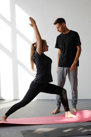El entrenador personal corrige a su cliente mientras hace ejercicios de yoga.