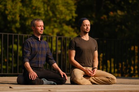 A yoga teacher and his student meditate while sitting in a lotus position on an open terrace. Outdoor yoga classes Stock Photo