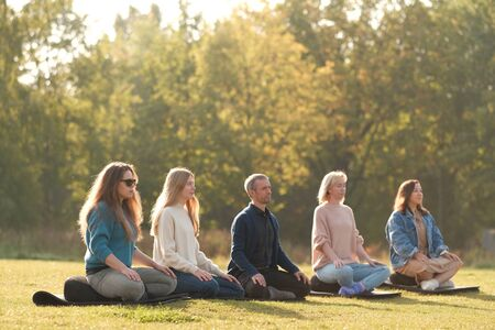 Group of young sporty people practicing yoga lesson with instructor, sitting in Padmasana exercise, meditating with closed eyes, Lotus pose