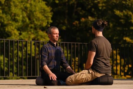 A yoga teacher teaches a young guy to breathe correctly during meditation. Outdoor yoga classes