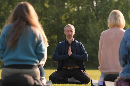 A yoga teacher shows an exercise for a group of beginners.