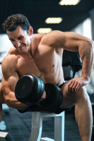 Gespierde man traint in de sportschool en doet oefeningen met halters, sterke mannelijke torso abs Stockfoto