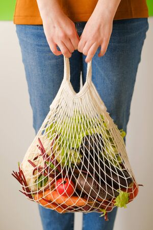 girl holds a rope bag with vegetables and fruits in her hands. Zero waste concept, reasonable consumption, shopping concept.