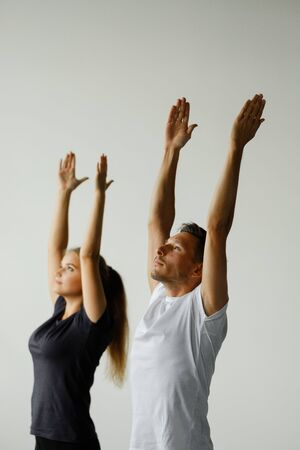 Beautiful sporty models a young woman and a young man in black sportswear are doing yoga. Models stand in the pose of Warrior I, Virabhadrasana 1 pose.