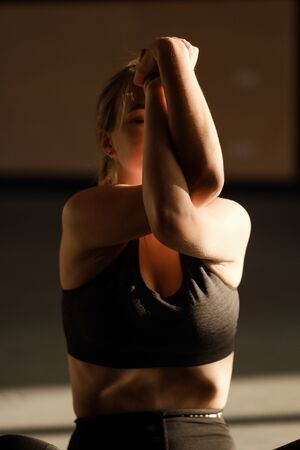 Young sporty attractive woman practicing yoga, working out, wearing sportswear, pants and top