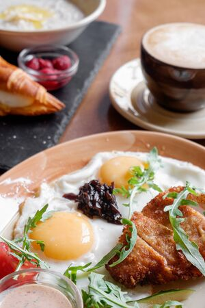hearty breakfast fried eggs breaded vegetables and coffee on a wooden table. healthy eating concept