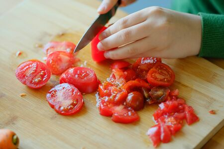 A young girl in a green sweater slices tomatoes to make a salad. The concept of healthy proper nutrition, diet. Veganism and Vegetarianism. Banco de Imagens