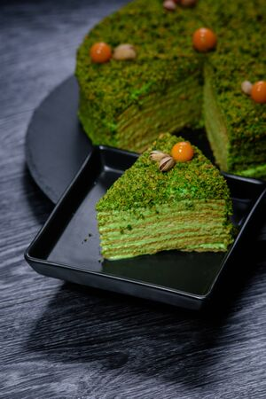 Tasty pistachio cake on a wooden table. close-up. dark background.