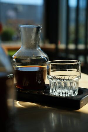 on the table is a jar of alternative coffee and a glass with coffee. Hario v60. concept filter Coffee. upright Stok Fotoğraf