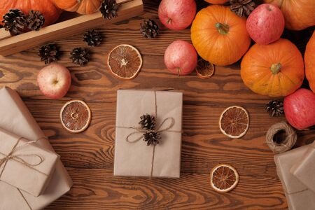 Gift boxes with pumpkins, garlands, apples and cones on a wooden table. Holiday, birthday, new year, christmas. Halloween holiday concept. holiday concept. Imagens