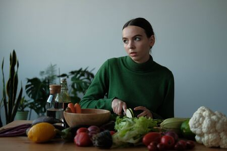 A girl in a green sweater cuts a zucchini knife with rings and slices on a wooden cutting board. On the table are carrots, cauliflower, tomatoes, lettuce - vegan products