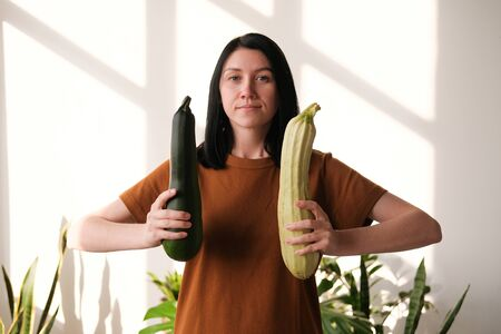 A young girl holds two zucchini in her hands. The concept of healthy eating, veganism and vegetarianism. Harvesting. World Vegan Day Reklamní fotografie - 132266305