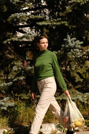 vegetables and fruits. shopping bag in the hands of a woman on a green background. Zero waste concept, reasonable consumption, shopping concept. Фото со стока