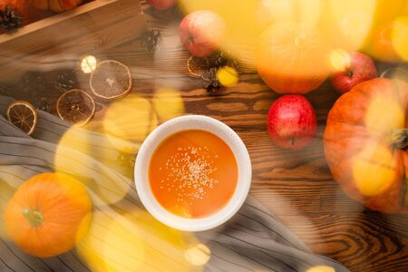 homemade pumpkin soup in glare on a wooden background with vegetables. Thanksgiving, veggie concept