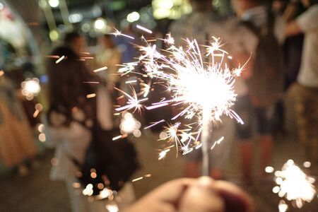 Hand with Sparkler. blurry sparks and background.close-up. party concept