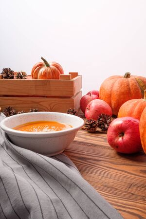 homemade fresh sweet pumpkin soup in a plate on a wooden background with vegetables. Thanksgiving, veggie concept Imagens
