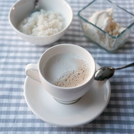 White cup of coffee with milk and rice porridge on the table. healthy eating concept. breakfast. view from above Stock fotó