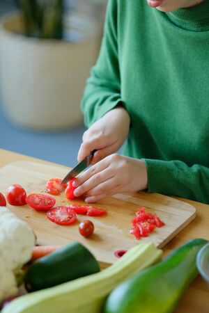 A young girl in a green sweater slices a knife with a knife on a wooden cutting board to make a salad. The concept of healthy proper nutrition, diet. Veganism and Vegetarianism. Banco de Imagens