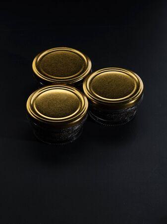 Glass jars with black sturgeon caviar. Black sturgeon caviar. Luxurious black caviar.