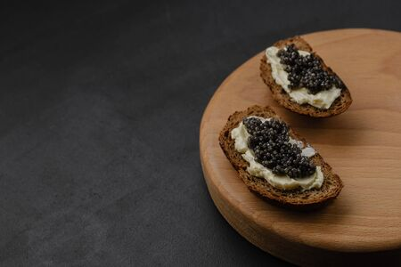 Sandwich with black sturgeon caviar on black background. Luxurious black caviar. Free space for text Stockfoto
