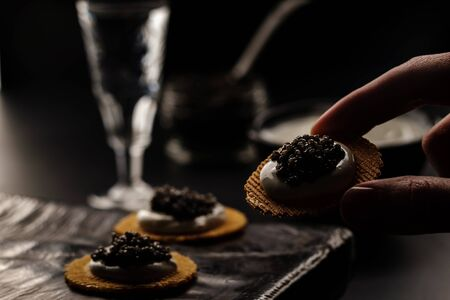 Sandwich with black sturgeon caviar on black background. Luxurious black caviar. Stockfoto