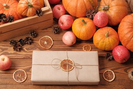 Gift boxes with pumpkins, garlands, apples and cones on a wooden table. Holiday, birthday, new year, christmas. Halloween holiday concept. holiday concept.