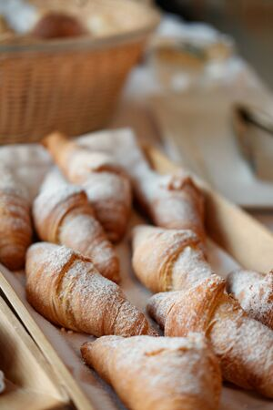 Many fresh croissants on a wooden tray. home bakery concept. Cafe. gluten free. top view