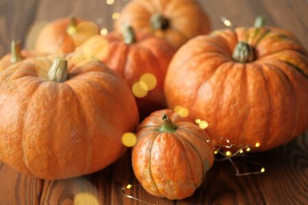 Halloween and Thanksgiving. Autumn concept. Orange pumpkins with a shining garland on a wooden table. Autumn background. side view. Fall season.
