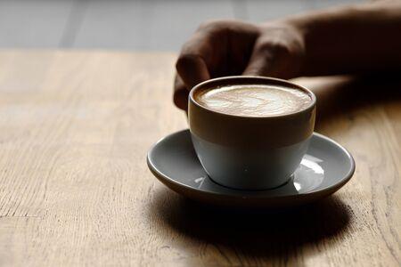 taza de capuchino en las manos. de cerca. luz tenue