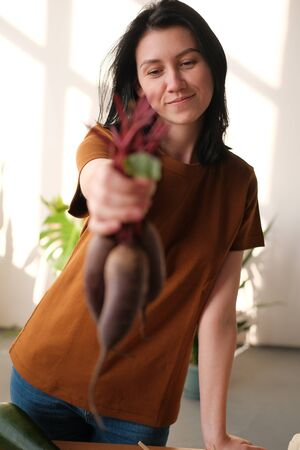 A young girl holds fresh beets in her hand. The concept of healthy eating, veganism and vegetarianism. Harvesting. World Vegan Day