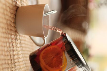 Hot red hibiscus tea with lemon. From a transparent teapot, tea is poured into a white cup. close-up