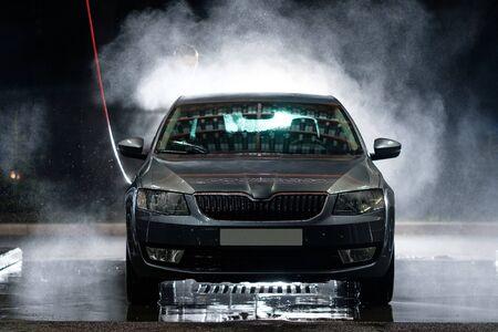 Przednia szyba samochodu z bliska. Czyszczenie samochodu wodą pod wysokim ciśnieniem. Zbliżenie samochodu. Myjnia samochodowa
