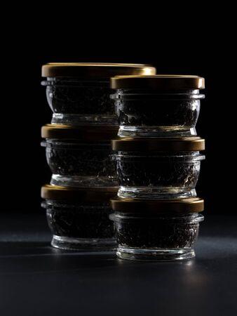 Glass jars with black sturgeon caviar. Luxurious black caviar.