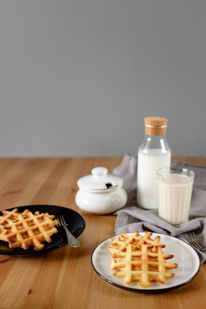 Viennese waffles on plates with a bottle of milk. side view. breakfast for two
