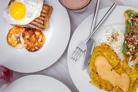 breakfast for two. fried eggs, toast, curd cheese, bruschettas with vegetables, and hash brown with sauce.White background. Banco de Imagens