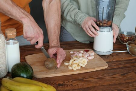 A man cuts kiwi into two to make a smoothie. On a cutting wooden board, sliced banana and sliced apple. Concept of healthy eating and dieting.