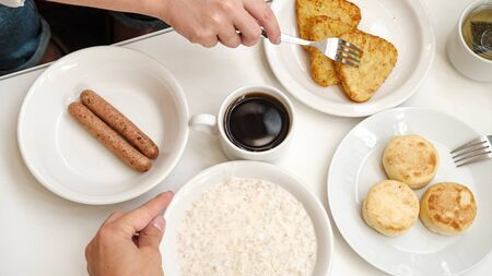 breakfast for two. cheese pancakes, oatmeal, sausages, hash browns and coffee. Hotel breakfast concept Banco de Imagens